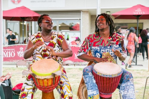 two african men playing djembe hand drums