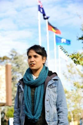Young Indigenous woman with aboriginal flag painted on her lips standing front of flag poles flying australian, aboriginal, and torres strait islander flags at Brimbank council's sunshine office