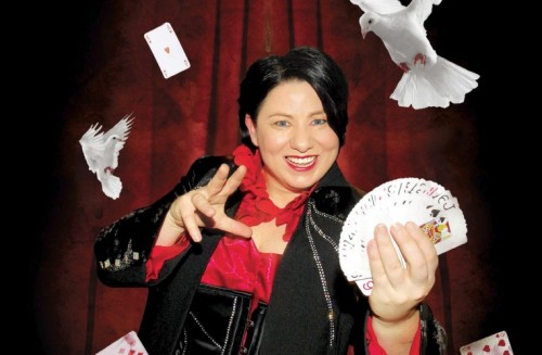 Magician Cath Jamison smiling and presenting a fan of playing cards in her hand