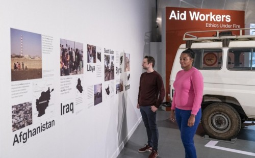 Two people viewing the Aid Workers exhibition