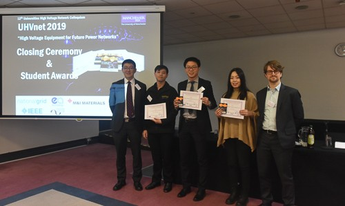 PhD students stand with their awards for best poster presentation
