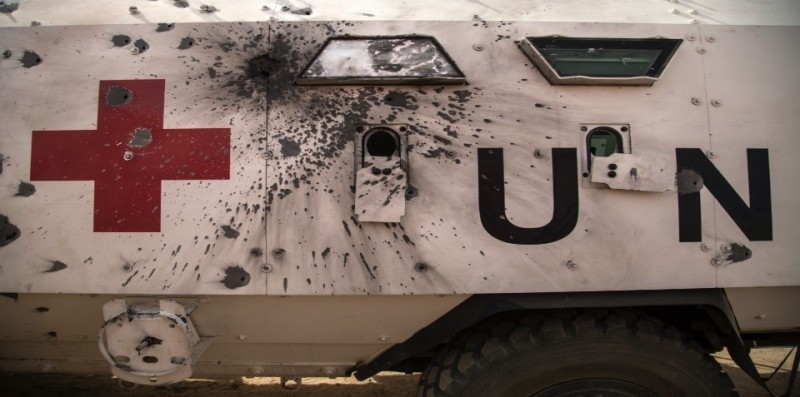 A United Nations aid vehicle with bullet holes scattered across.