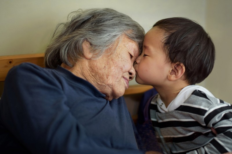 A baby kissing an elderly lady