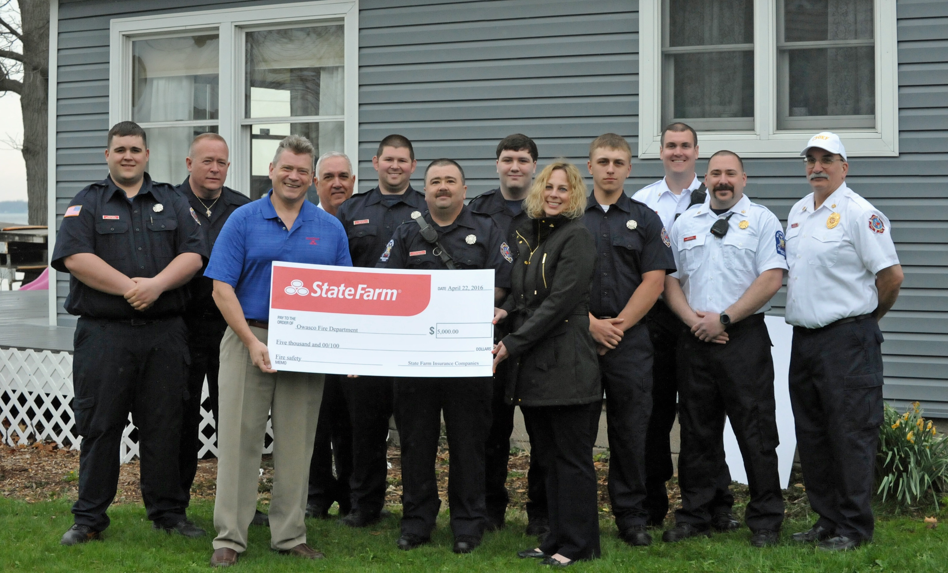 Firemen and State Farm posing with giant check