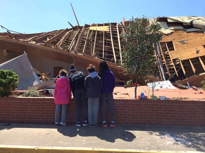 Individuals viewing the remains of Aim High Academy's practice center.