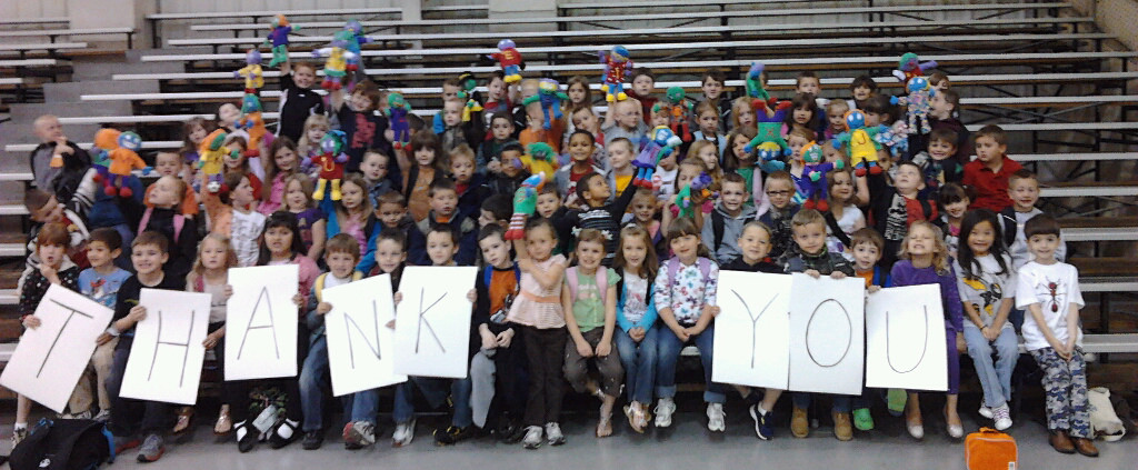 Large group of 2nd graders in school bleachers holding thank you sign