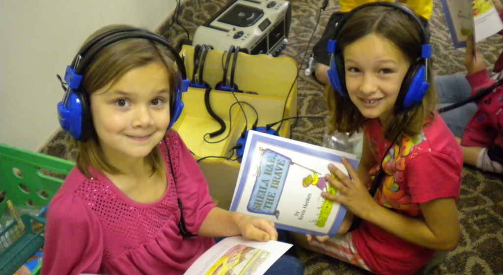 Two second grade girls listening to an audio book with headphones on.