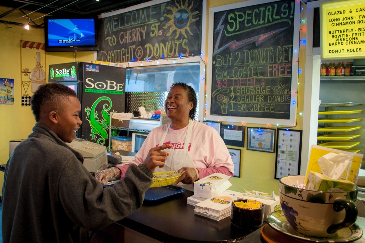 Woman behind counter laughing with a young man who is her customer at the donut shop.