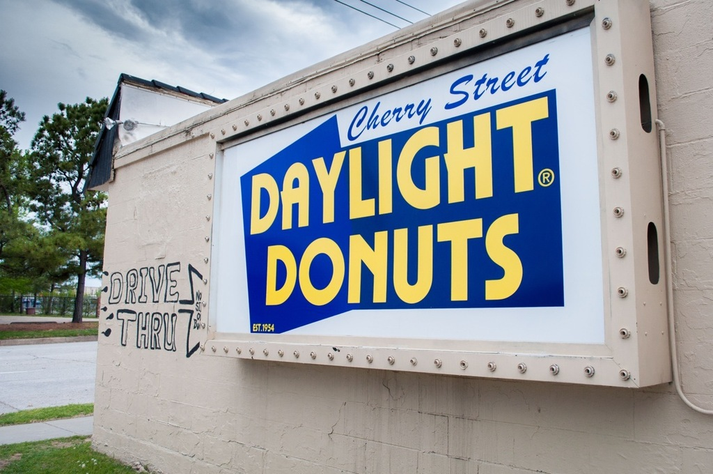 Side of building with business sign that reads Cherry Street Daylight Donuts.