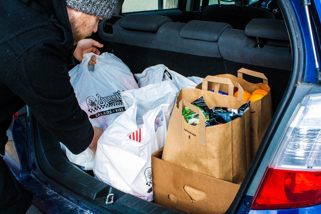 Ed Beebe retrieving packaged food from am automobile trunk.