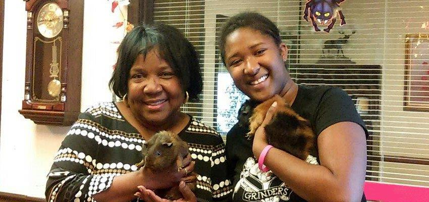 Etta McKenzie rescued a customer's tiny family members after they suffered smoke inhalation in a fire. Belgium, left, and Donovan, held by owner Alyssa, were all thankful Etta took the guinea pigs under her wing for the night.