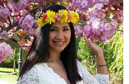 A photo of Selena Martinez smiling next to a flowering tree and with a band of flowers around her head.