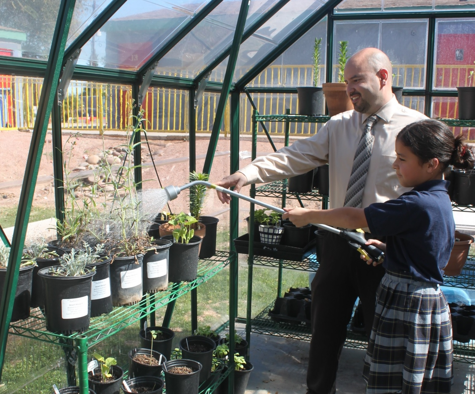 Principal Adam Sharp and a student watering plants.