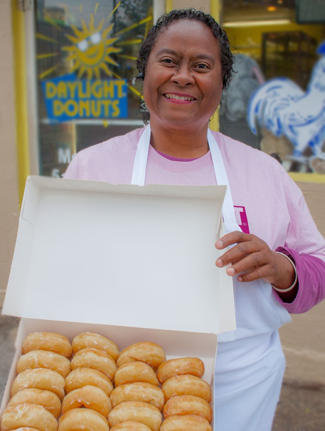 Debra Dickens Holmes holding a box of glazed donuts.