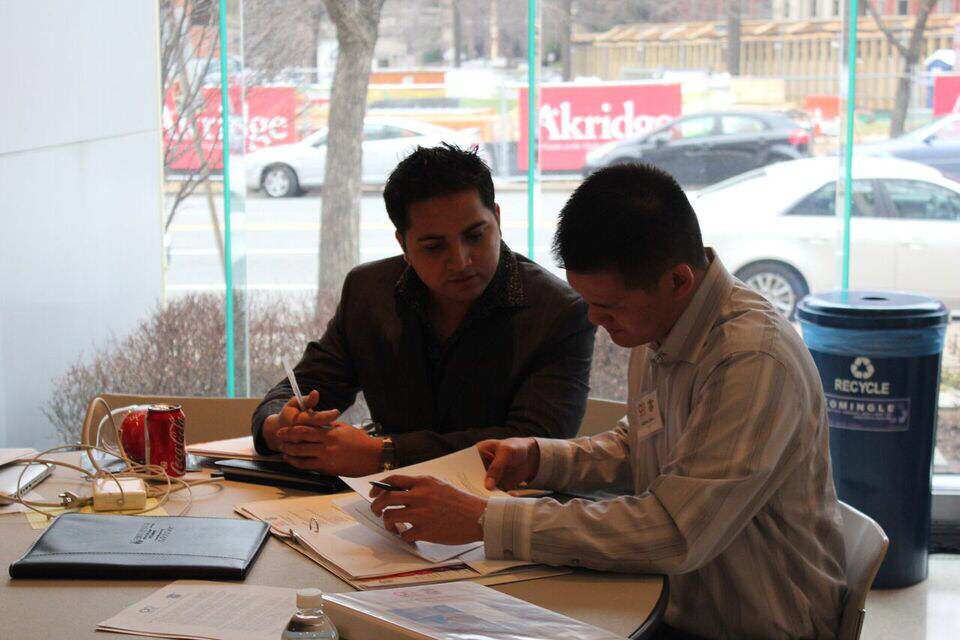 Hari Adhikari helping someone with paperwork.