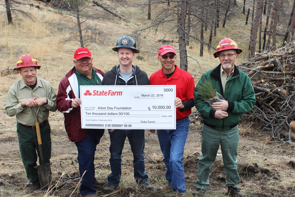 Arbor Day Foundation men holding a check from State Farm for $10,000.