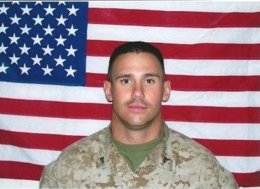 Cpl Jared Shoemaker pictured in front of the American flag.
