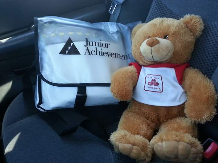 A junior achievement tote bag next to a stuffed state farm goodneighbear in the back seat of a car