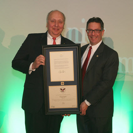 Two gentlemen in suits one is holding a framed award given by the other man