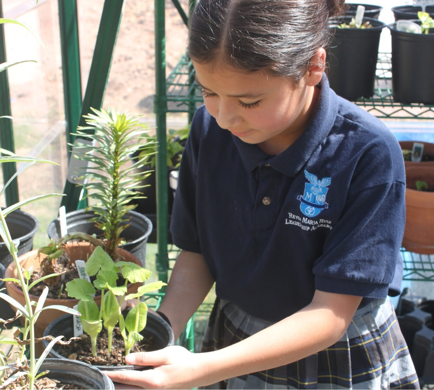 Student at Reyes Maria Ruiz Leadership Academy holding a plant.