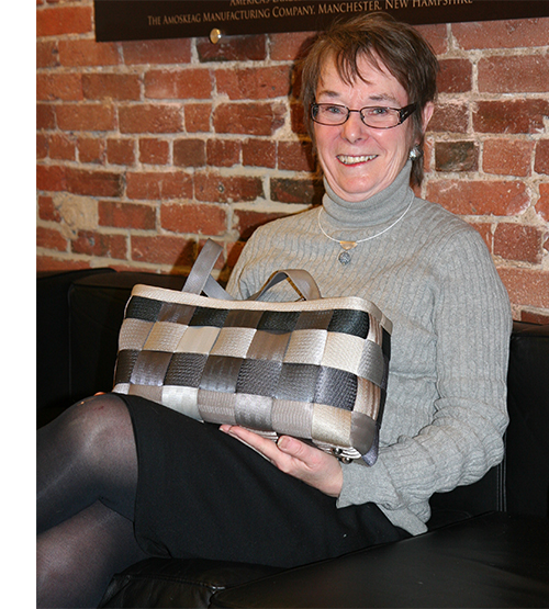 Women sitting next to a brick wall holding a purse made of seatbelts.