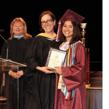 Selena Martinez in her cap and gown smiling as she is being presented her high school diploma by two school officials