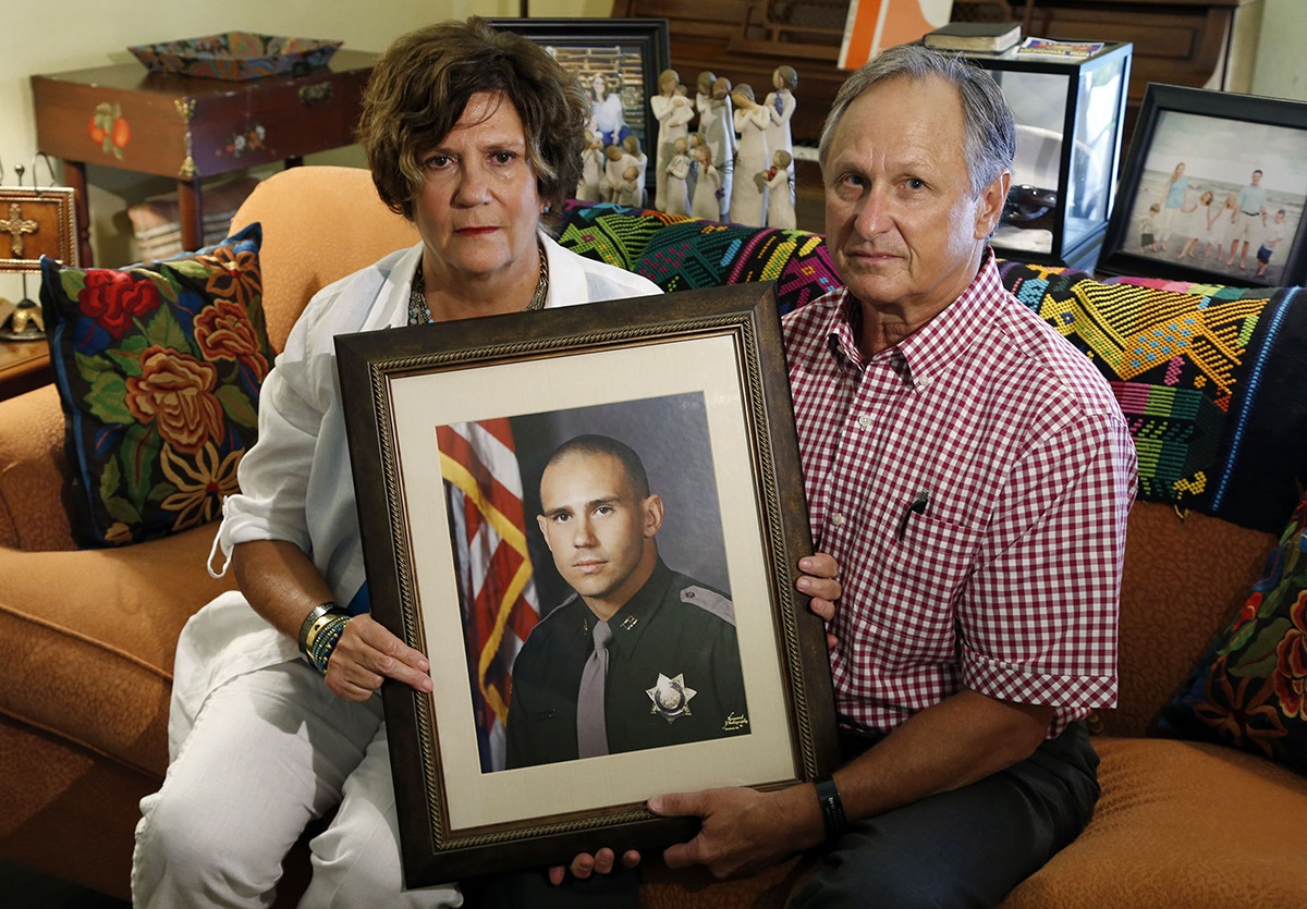 Linda and Ken Shoemaker hold a photo of their late son, Corporal Jared Shoemaker.