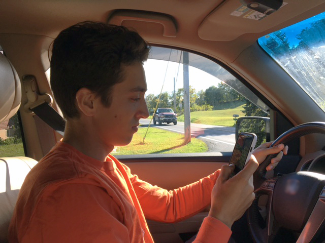 teen driver behind the wheel looks at his phone as an oncoming vehicle approaches