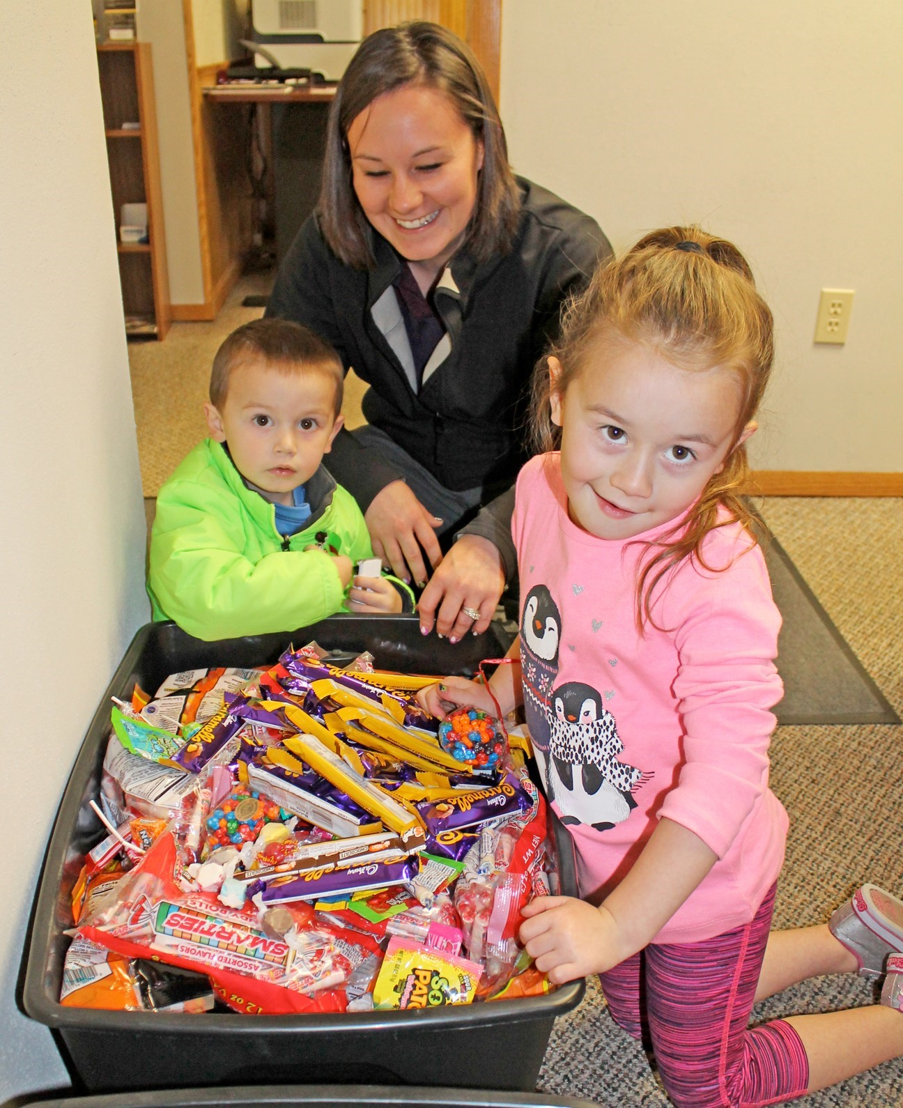 Smiling woman with two small children hovering over a plastic bin of Halloween candy