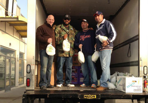 Picture of four men holding Thanksgiving turkeys in their hands standing in the back of a box truck smiling.