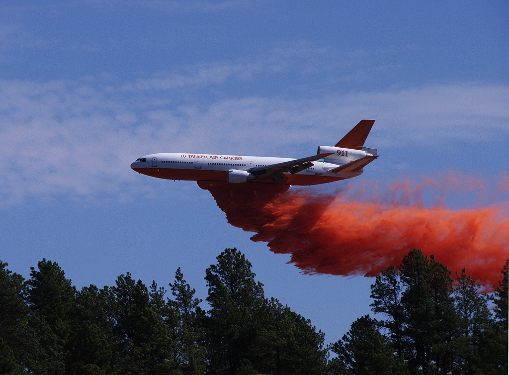 Plane dumping fire retardant on forest fire