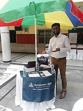 Krishna Prasanth standing at a GSU recruiting booth in India