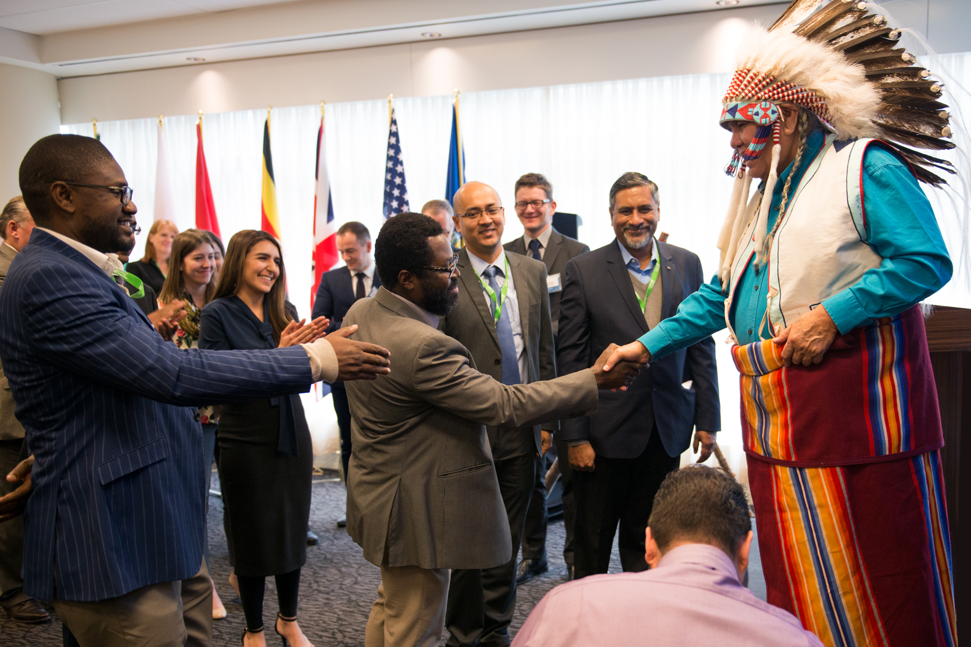 Blackfoot elder Dr. Reg Crow Shoe chats with delegates following a smudge ceremony.