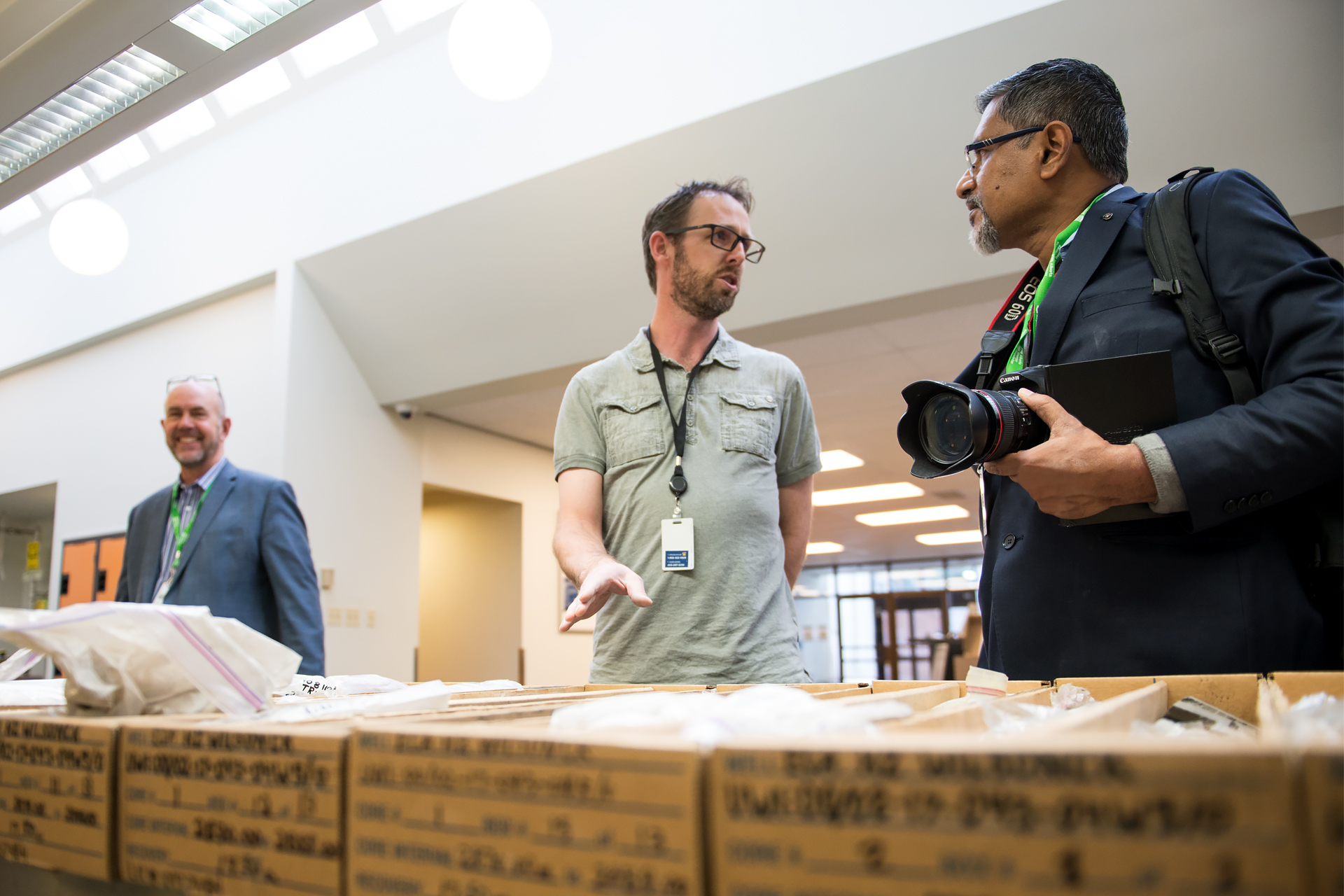 A delegate from India discusses shale core samples with a Core Research Centre employee.