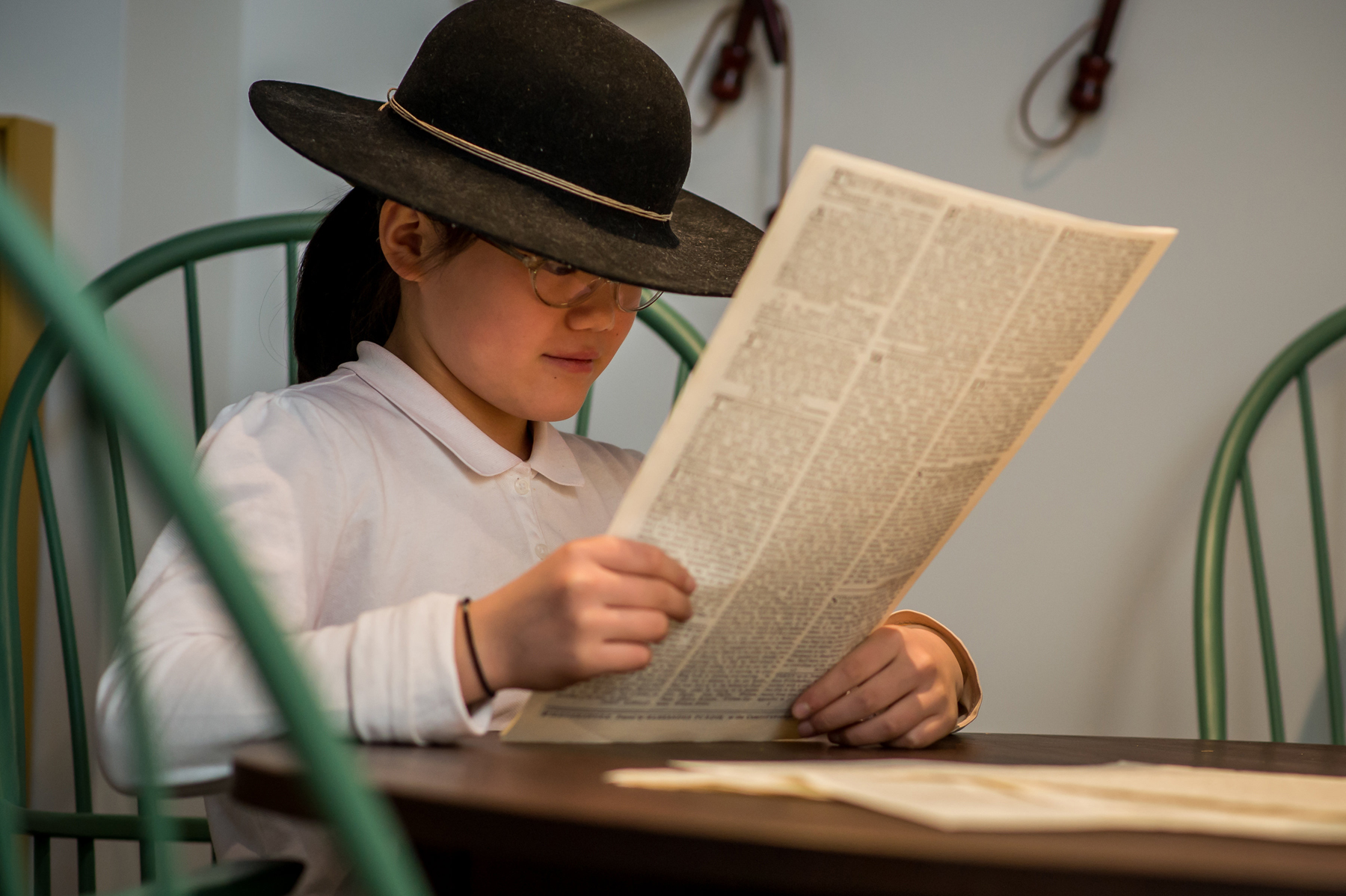 Youth reads 18th Century newspaper at Museum of the American Revolution