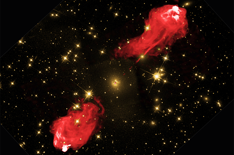 Two images of Cygnus A layered over each other to show the galaxy's jets glowing with radio radiation (shown in red). Quiescent galaxies, like our own Milky Way, do not have jets like this, which may be related to magnetic fields. The yellow image shows background stars and the center of the galaxy shrouded in dust when observed with visible light. The area SOFIA observed is inside the small red dot in the center. Credit: Optical Image: NASA/STSiC Radio Image: NSF/NRAO/AUI/VLA