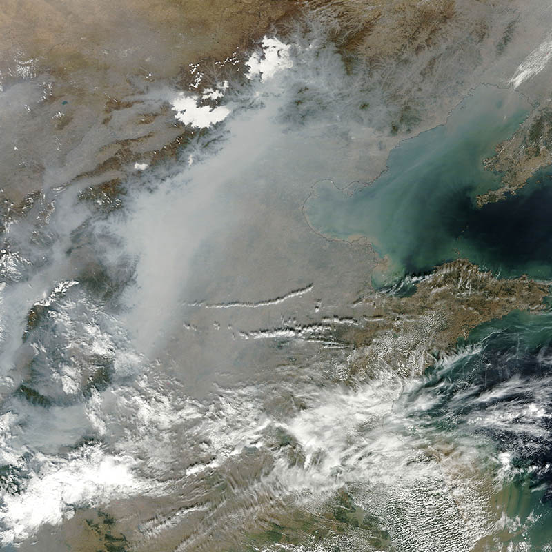 A thick layer of haze blanketed the North China Plain on October 9, 2014, when the Moderate Resolution Imaging Spectroradiometer (MODIS) on NASA's Terra satellite acquired this natural-color image at 2:50 Coordinated Universal Time (10:50 a.m. local time). The haze obscured many features usually visible in MODIS imagery of the area, including China's largest city, Beijing. Credit: Jeff Schmaltz, LANCE MODIS Rapid Response. Caption by Adam Voiland.