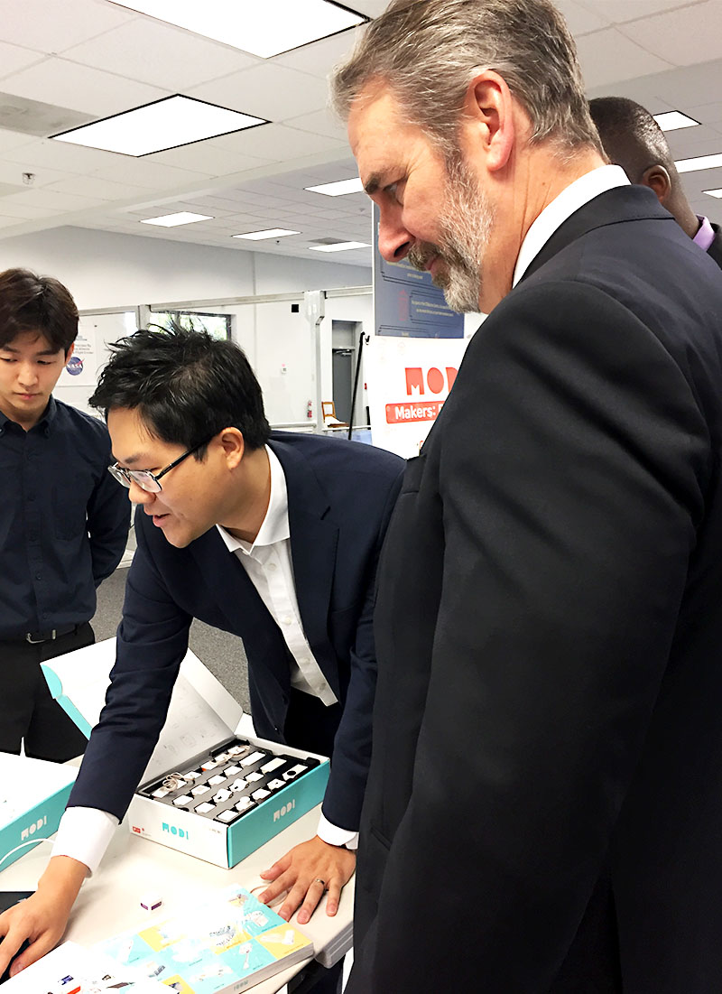 Dr. Jeffrey A. Isaacson, CEO and President, USRA (right) watching Jastin Tech CEO, Dr.;SangHun Oh demonstrate; the operation of the MODI Robotics components.