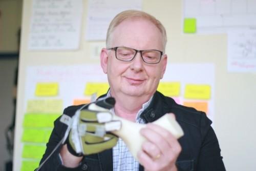 Fred Holtkamp demonstreert de handschoen met sensoren.