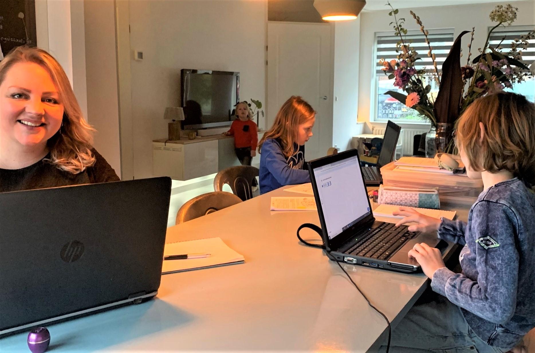 Nienke van Vugt-Oelen thuis aan het werk met naast haar dochter Jip, tegenover haar zoon Abel en op de achtergrond zoon Bijs.