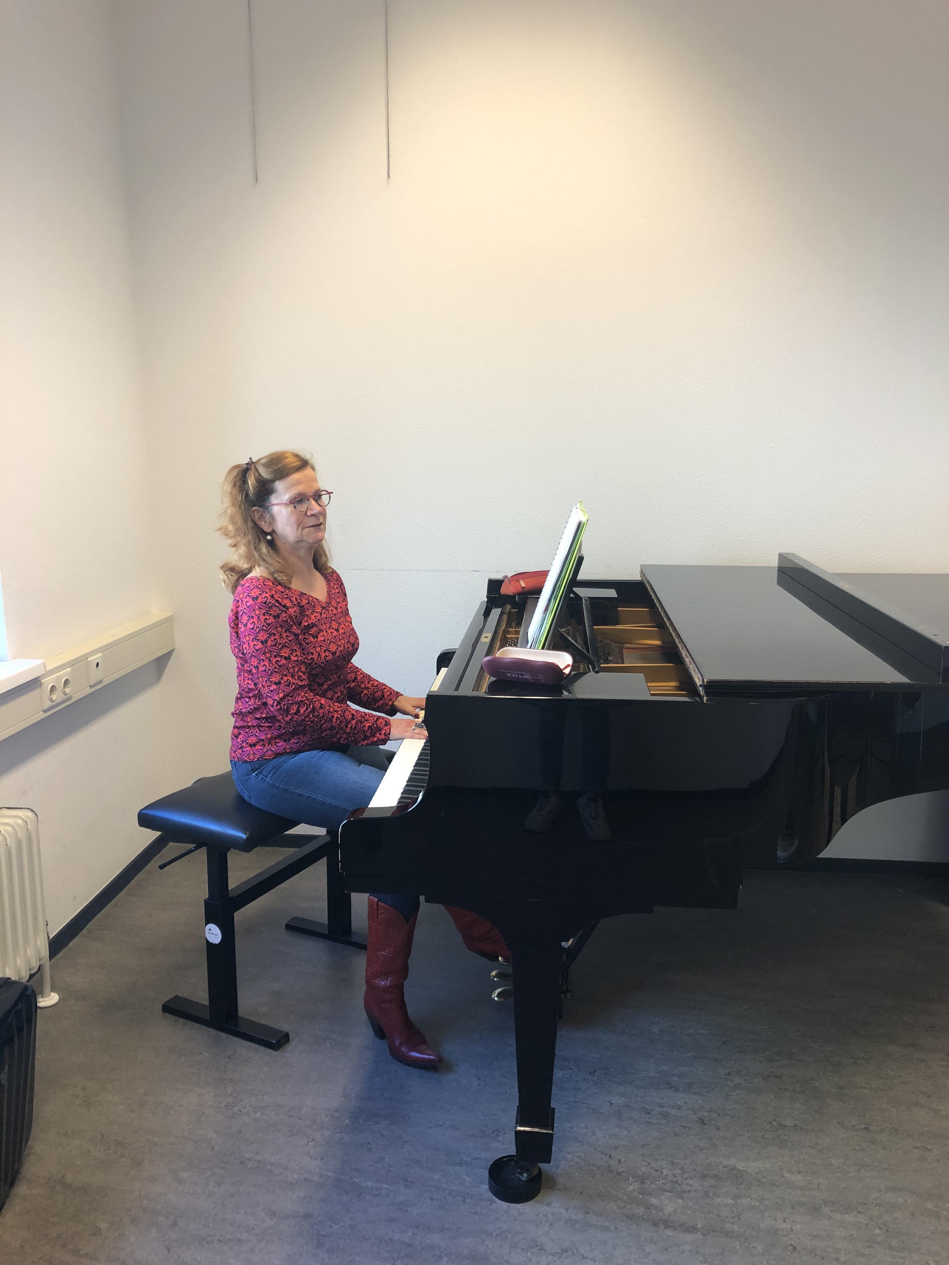 Zangdocent Peggy Hegeman begeleidt studenten op de piano.