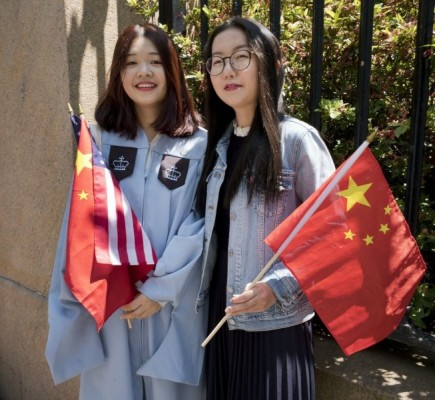 Two students from China celebrate their 2019 graduation from Columbia University in New York. AP Photo/Mark Lennihan