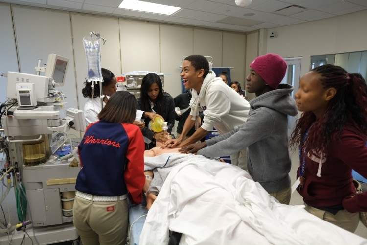 Students from Eastmoor Academy practice compressions at Ohio State