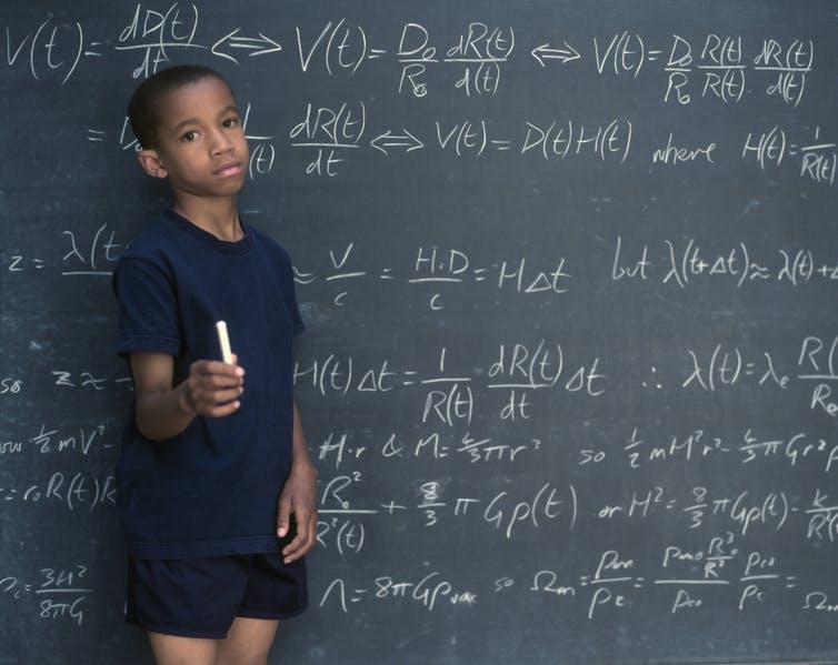 Black student at chalkboard.