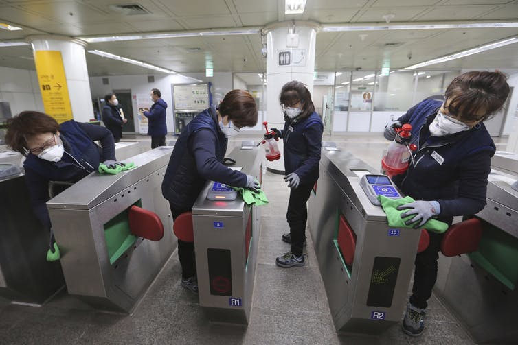 Employees disinfect ticket gates in South Korea.