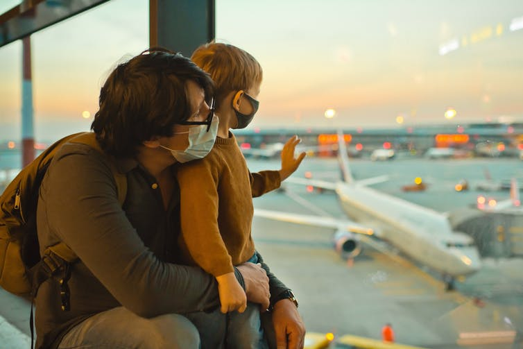 Man and son looking at planes through window at airport.
