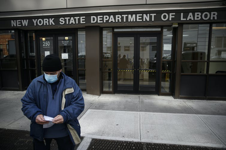 Man stands in front of unemployment office in New York.