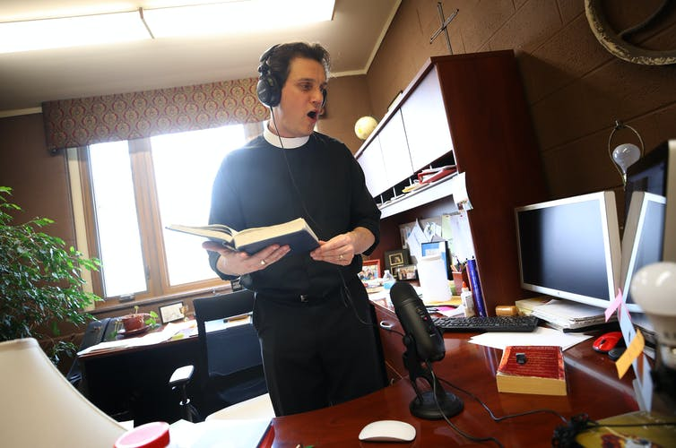 The Rev. Philip Dinwiddie sings to a pre-recording of mass at St. James Episcopal Church in Grosse Ile, Michigan.