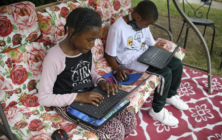 two children on laptops in their home.