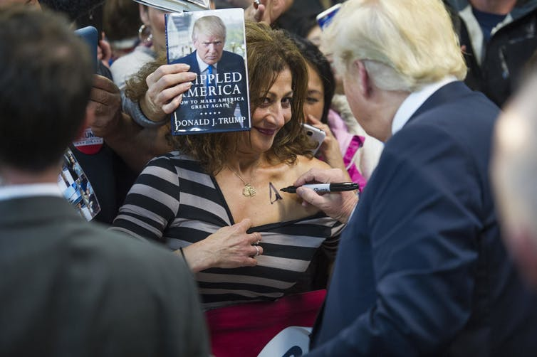 Trump autographing a woman's chest after a campaign rally in 2015.